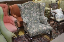 A George III style mahogany framed wing chair, early 20th century, with broad stuffed-over seat