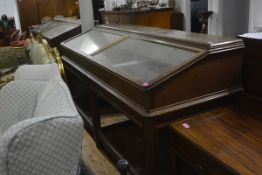 A large glazed oak display cabinet, with moulded rectangular top above a pair of glazed slant-