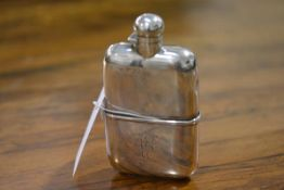 An Edwardian silver hip flask, London 1902, shaped for the hand, with screw top and detachable