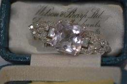 A diamond plaque brooch in the Art Deco taste, centred by a large square cut pale pink stone, (