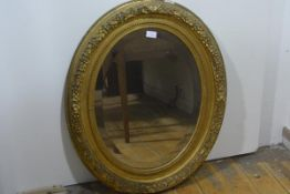 A 19th century oval gilt-composition frame, moulded with ribbon-tied leaves and berries and now