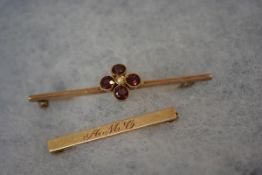 An Edwardian 9ct gold bar brooch, set with rubies and a seed pearl in a flowerhead pattern; together