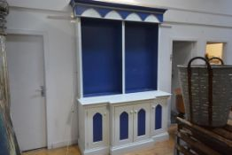 A large painted breakfront open bookcase in 18th century style, the upper section with Gothic arch