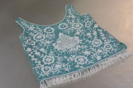 A 1960's heavily beaded sleeveless evening top, with white beadwork against a blue ground, label