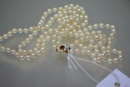 A twin-strand cultured pearl necklace, the uniform pearls on a ruby and pearl 9ct gold clasp. 59cm