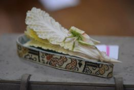 A Chinese ivory carving of a grasshopper on a cabbage, vestiges of colour, on a silk stand contained