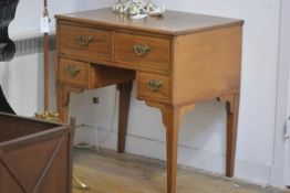 A George III style inlaid mahogany lowboy, the rectangular top decorated with paterae over an