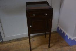 A George III style inlaid mahogany bedside cupboard, with frieze drawer over a cupboard door, on