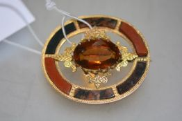 A late Victorian hardstone brooch set in yellow metal (unmarked), centred by a stone of Cairngorm
