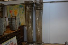 An imposing pair of carved wooden columns, fluted, with leaf and scroll carved capitals, on square