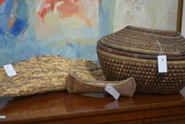 A group of tribal artefacts comprising two model canoes and a covered basket (3)