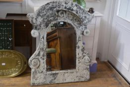 A distressed painted metal mirror, scroll form decorated with flowerheads, enclosing an arched