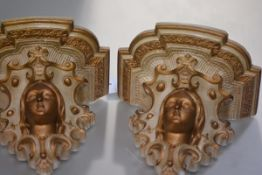 A pair of parcel-gilt plaster wall brackets, c. 1900, each with shaped shelf above a female mask