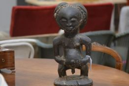 A large African tribal carved wooden figure, probably West African, the seated male with prominent