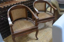 A pair of Colonial style teak-framed canework open armchairs, raised on cabriole legs.
