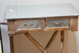 A contemporary side table with polished metal top over two drawers on distressed painted folding