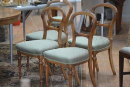 A set of four Victorian walnut balloon back chairs, each with incised ebonised decoration, on
