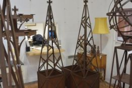 A pair of weathered cast steel garden obelisk planters, each with fleur de lys finial over an x-form