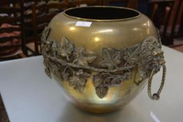 A large late 19th century brass jardiniere, applied in high relief with a band of grapes and vines