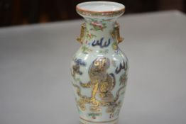 A Chinese celadon porcelain baluster vase, enamel painted with a dog of fo amidst blossoming sprigs,