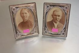 A pair of hallmarked silver photograph frames in the Edwardian taste, each with oval aperture, the