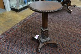 A good George IV rosewood occasional table, the circular top with boldly carved gadrooned edge, on a