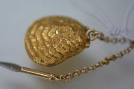 A 19th century yellow metal (possibly 9ct gold) clamshell locket, on a lapel chain, glazed