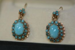 A pair of late 19th/early 20th century turquoise pendant earrings each set to the centre with an
