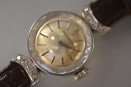 A vintage lady's Movado dress watch, the circular gilt dial with baton numerals within a white metal