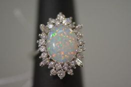A striking opal and diamond ring, the oval-cut opal claw set within a sunburst band of round