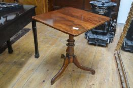A George III mahogany tilt top tripod table, the square top on a turned baluster standard and