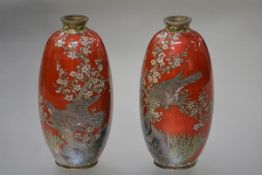 A pair of Meiji period cloisonne vases, each of ovoid form, decorated with birds perched in