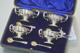 A cased set of four George V silver salts, Birmingham 1912, each twin-handled, with spoons.