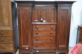 A small 19th century mahogany compactum wardrobe with overhanging cornice above an inverted