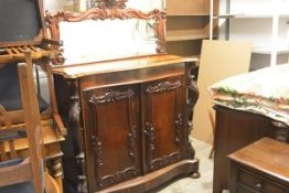 A mid-Victorian rosewood chiffonier, the mirror back with a boldly scroll-carved frame above a