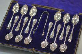 A cased set of twelve George V silver teaspoons with tongs, Sheffield 1912, decorated with bands