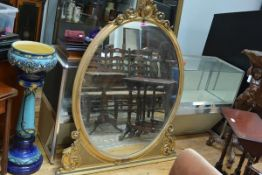 An unusual 19th century gilt-composition overmantel mirror, the oval plate within a conforming frame