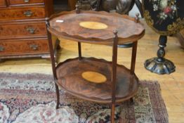A George III style satinwood inlaid mahogany two tier occasional table, the oval tray top centred by