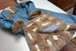 A man's fur-lined silk coat, probably Chinese, early 20th century, the patterned teal silk with knot
