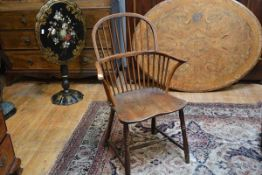 A 19th century yew and elm Windsor armchair, the low hoop back above a dished seat flanked by