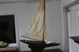 A large early 20th century painted wooden pond yacht, fitted with metal rudder, main and jib
