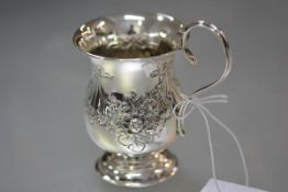 An Edwardian silver christening mug, Birmingham 1903, of baluster form, chased with ribbon-tied
