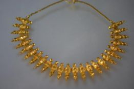 An Indian yellow metal (probably high carat gold) fringe necklace, composed of shaped baluster