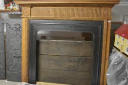 A Regency style pine chimneypiece, the overhanging shelf above a fluted central panel flanked by