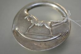Hermes, a sterling silver rattle, of padlock form, repousse with a rocking horse, stamped marks