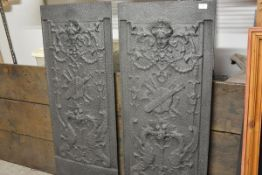 A pair of large cast-iron panels, in the Elizabethan taste, each with female mask above a trophy