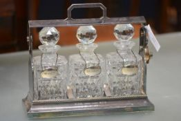 A silver-plated three-bottle tantalus, the three decanters each with silver-plated label, in a