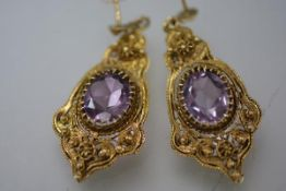 A pair of amethyst drop earrings, each with oval-cut stone claw-set within a scrolling yellow