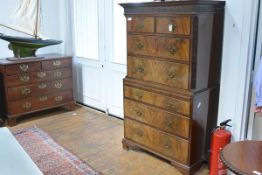 A George III style walnut chest on chest, with dentil-carved cornice above a blind fretwork