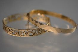 A 9ct yelllow gold bangle, in the Art Nouveau taste, pierced with stylised foliated motifs; together